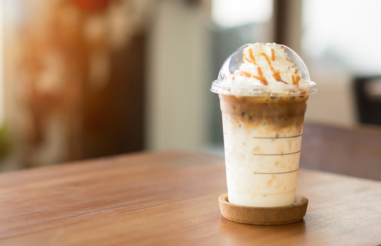 Ice coffee and whipped cream with caramel sauce on table