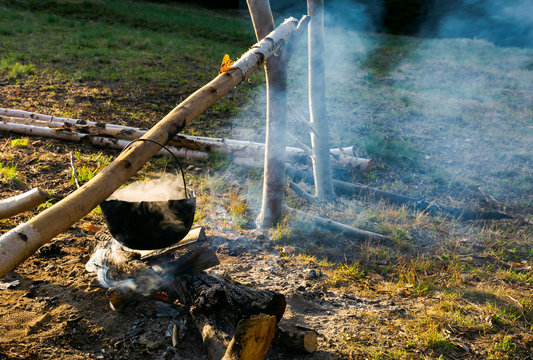 making food in cauldron on fire. steam and smoke all over the place