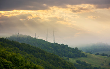 foggy autumn countryside in mountains. power line tower on the forested hill touch the cloud. beautiful golden light