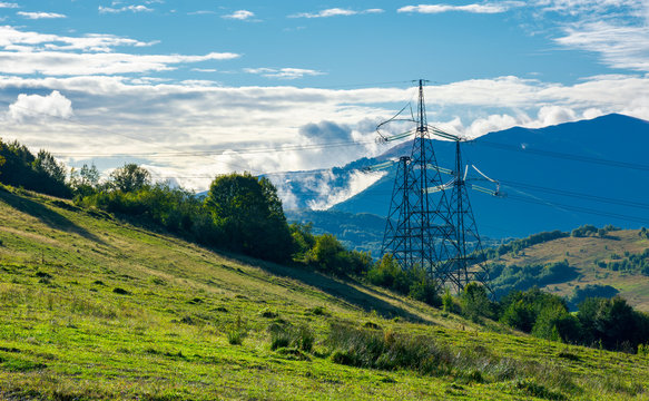 power line tower on the hill. huge mountain in clouds in the distance. autumn countryside