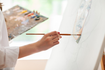Hand of artist with brush painting picture