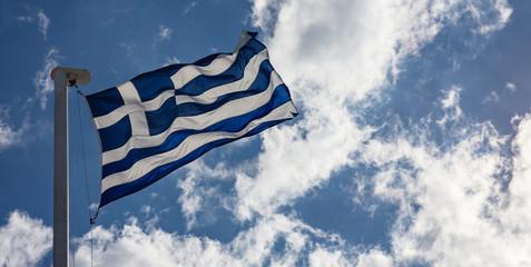 Greek flag on flagpole waving on blue sky background
