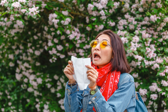 Allergy concept. Young asian woman sneezes and blowing her nose with a handkerchief and suffering in the spring among flowering and blooming trees.