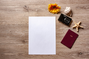 Flatlay holiday /travel theme with brown background with camera,passport,shell ,starfish and flowers