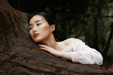 Young Asian lying on tree