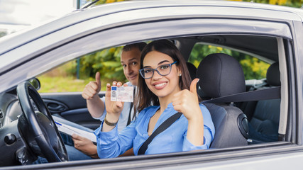 Driving school. Beautiful young woman successfully passed driving school test. She looking sitting in car, looking at camera and holding driving license in hand. Fototapete