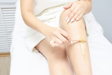 Waxing woman leg. Sugar hair removal. laser service epilation. Salon wax beautician procedure