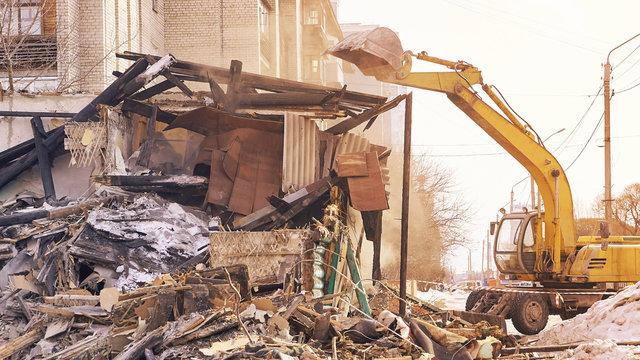 Demolition house using excavator in city. Rebuilding process. Remove equipment