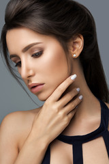 Studio portrait of beautiful woman with hairstyle and professional make up with hand manicured with white nails over grey background.