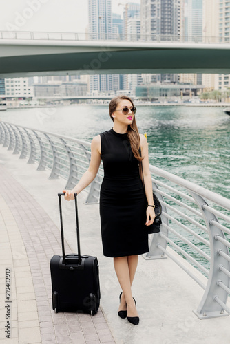 young modern confident business woman pulling a suitcase in a dubai