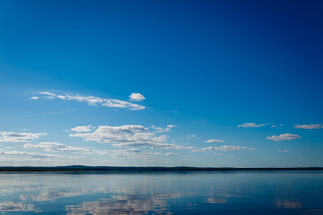 Blue sky with clouds over Lake Ladoga. Beautiful landscape with deep blue sky and quiet lake without excitement.