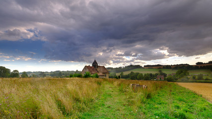 Summer stormy sunset over St Hubert's Church at Idsworth, near Finchdean in the South Downs National Park, Hampshire, UK