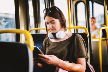 Cute smiling girl looking on a telephone in u public transportation.