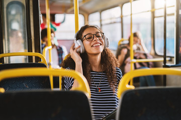 Curly smiling girl enjoying music in bus.