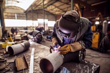 Industry male worker in protective uniform repairing metal pipe.