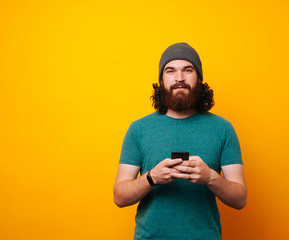 Young bearded long haired hipster man using phone looking at the camera on yellow background.