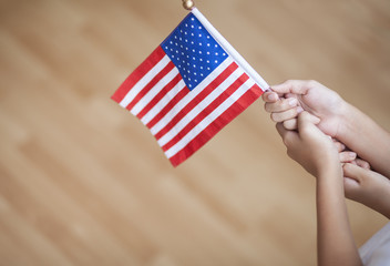 Boy hand holding American flag, on wooden background.