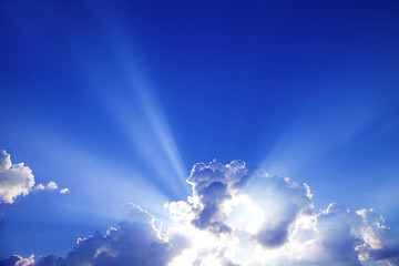 sun rays with clouds on blue sky landscape.