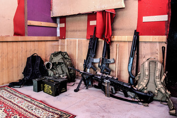 U.S. army marines assault squad weapon storage at outpost with service rifles, combat shotgun, tactical backpacks and ammunition boxes, sniper rifle with optical sight and machine gun with ammo belt