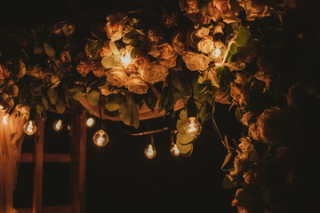 Closeup view of top of beautiful floral night wedding decorations with soft light of lamps. Outdoor reception holiday decor. Horizontal color photography.