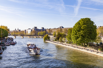 France, Paris, Tourist boat on Seine river with Louvre in background
