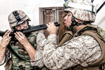 Army soldier blowing cigarette smoke in combat shotgun chamber while his comrade inhaling smoke from gun barrel. United States Marine Corps infantries smoking marijuana with service pump-action rifle