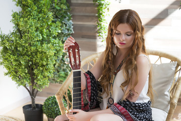 A beautiful girl with red curly hair sits on a chair with a seven-string guitar.