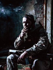 Tired after hard battle army soldier, exhausted with fight Navy Seal rifleman sitting with assault rifle on knees, resting and smoking cigarette in abandoned building, low key, high contrast shoot