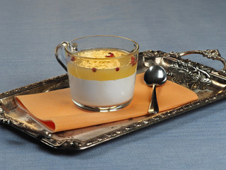 A cup of panna cotta with orange jelly and pink peppercorns set on a silver tray