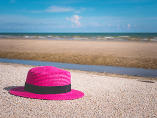 Beautiful women's hat on the beach during summer.