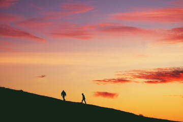 2 Silhouette persons Walking Up Hill Mountain Climb Sunset