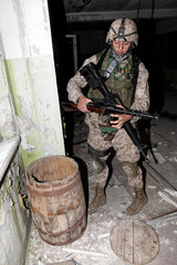 U.S. marine, special forces soldier holding in hands and examining automatic weapons of World War II, found in wooden barrel at old, abandoned building during anti terrorist raid or clearing mission