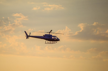 Silhouette of helicopter flying against amber sky during sunset over sea