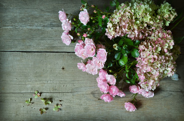 Bouquet of roses and  hydrangea on wooden background. Greeting card