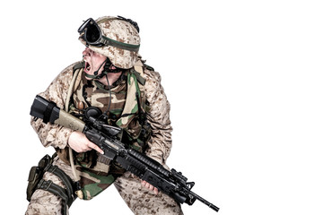 Studio shoot of modern infantry soldier, U.S. marine rifleman in combat uniform, helmet and body armor, screaming and crouching down with assault service rifle in hands isolated on white background