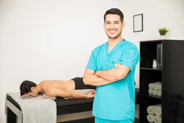 Smiling Physiotherapist Standing Arms Crossed With Patient In Background