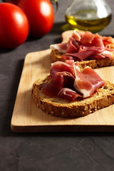 Spanish ham (jamon) on a piece of toasted whole grain bread, tomatoes and olive oil beside
