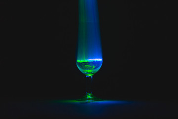 Glass cup full of blue and green light in front of black background