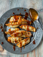 Asian pot stickers with drizzled sauce on plate