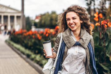 Happy girl with curly hair enjoy drink outdoor