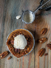 mini pecan pie with scoop of vanilla ice cream on rustic table