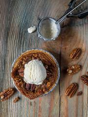 mini pecan pie with scoop of vanilla ice cream on rustic table