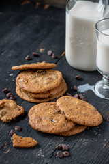 chocolate chip cookies with milk on rustic wood table