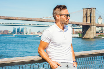 European Man traveling in New York, with beard, little gray hair, wearing white Polo shirt, sunglasses, standing by East River, looking around, thinking. Manhattan, Brooklyn bridges on background..