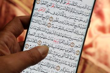 Jeune femme lisant le Coran sur son téléphone portable. / Young woman reading the Koran on her mobile phone. Wall mural