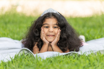 A young girl holding her head is laying on the green grass