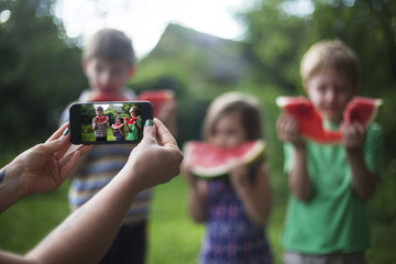 Female hands taking photo of cheerful happy children eating watermelon