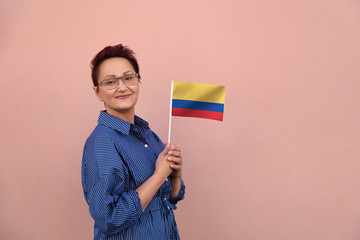 Colombia flag. Woman holding Colombian flag. Nice portrait of middle aged lady 40 50 years old with a national flag over pink wall background outdoors.