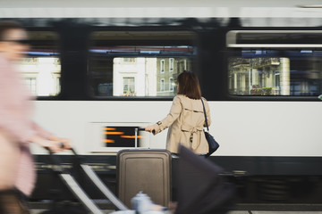 A girl is wating a train in a trian station at Geneva, Switzerland.