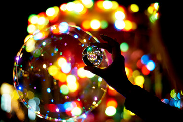 Glass ball in hand, reflection of lights and bokeh. Amusement park